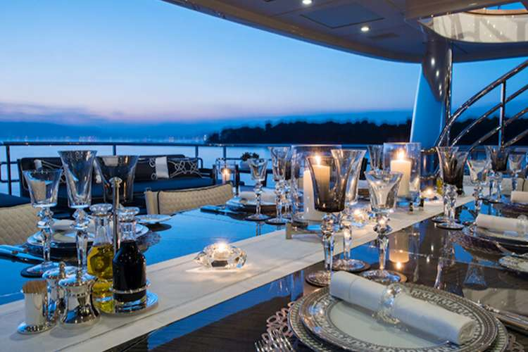 Table set with Boutsen Design glass and table ware on a superyacht deck in the evening