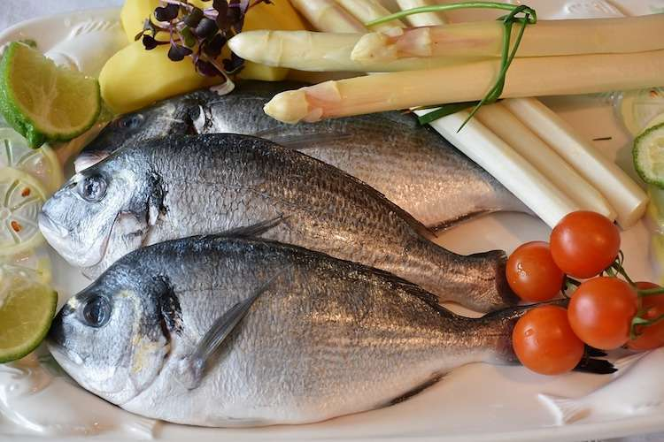 Image of fresh fish displayed with asparagus. lemon, and tomatoes