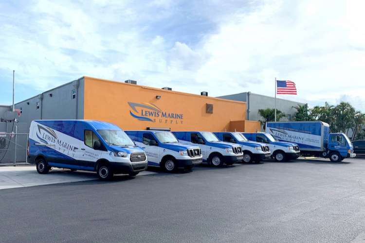 The Lewis Marine Supply building and Lewis marine vans parked in front of it in a row