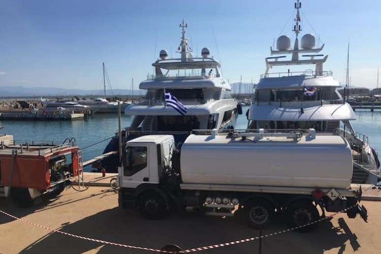Superyacht services bunkering trucks in a dock servicing superyachts