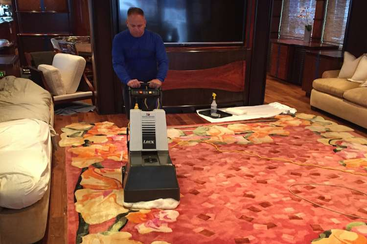 JC's Carpet Cleaning expert cleaning a superyacht carpet.