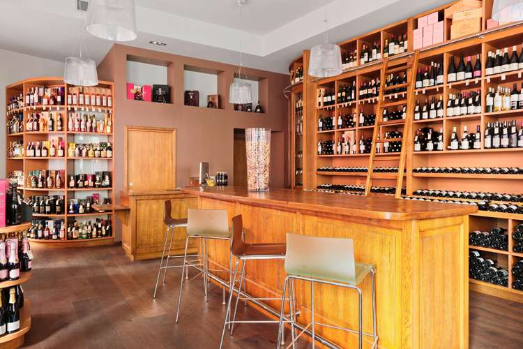Wine cellar with wine bottles on the shelves and a bar with chairs for wine tasting