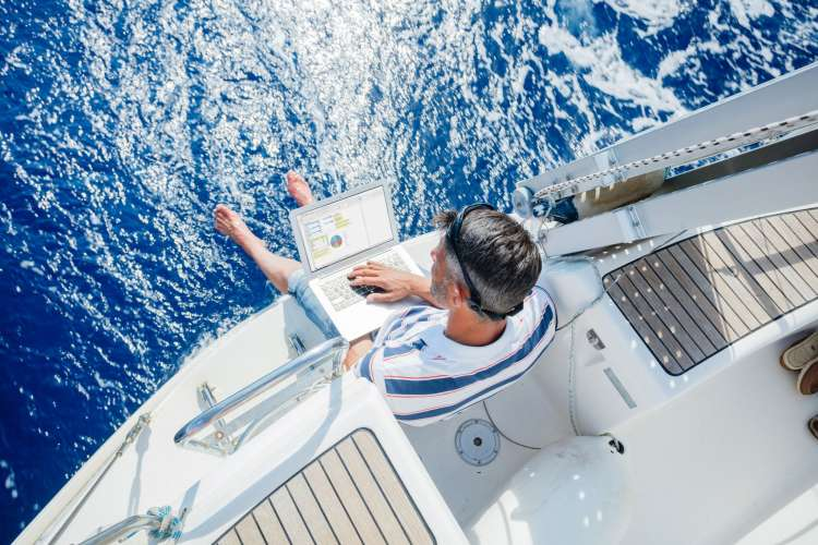 Man sitting in the stern of a yacht with a laptop on his lap feet hanging over the blue sea.