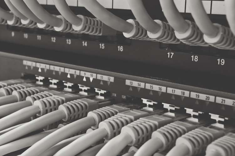 Image of a server rack cabinet full with cables.