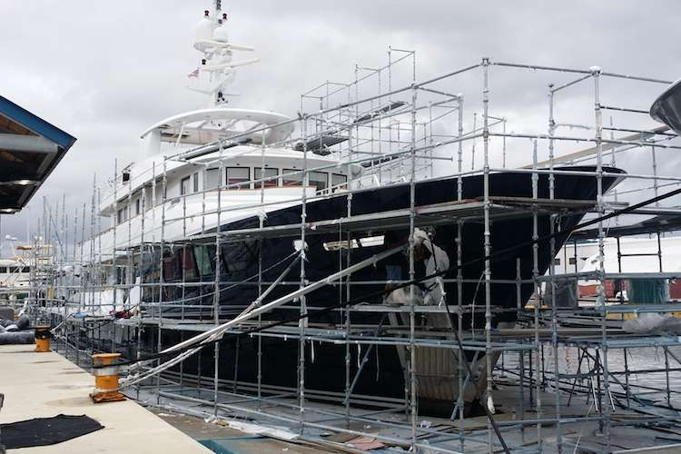 A superyacht dry docking in a shipyard surrounded by scaffolding