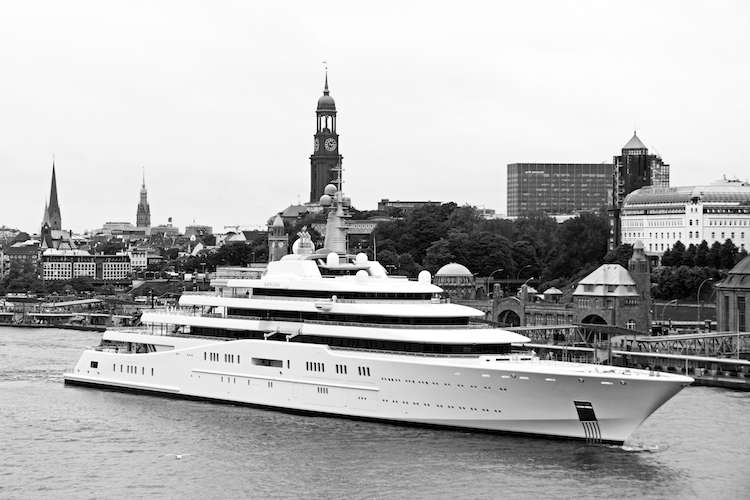 Black and white image of a mega yacht in front of a city shore.