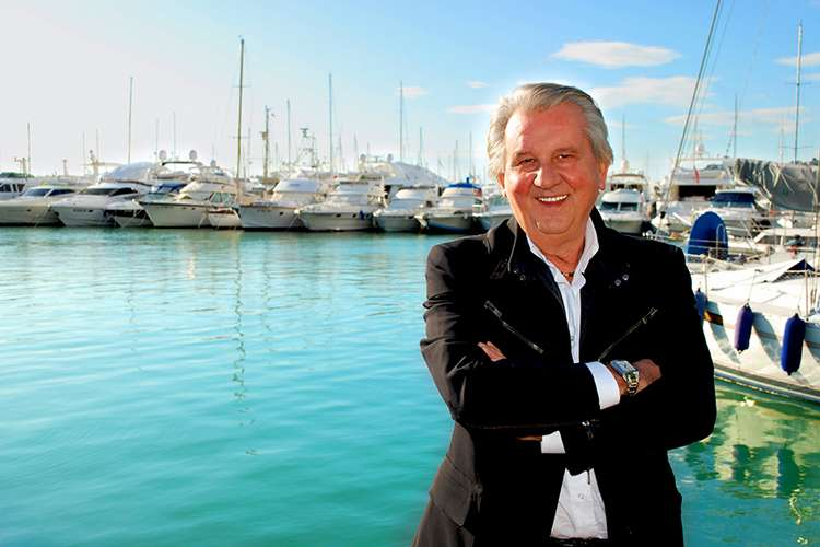 The founder Dr. Sartore smiling arms folded with a superyacht port in the background.