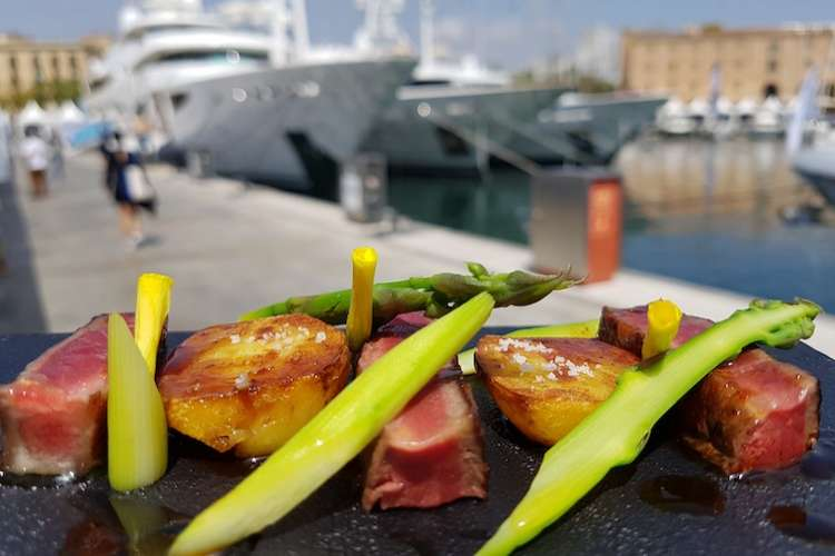 Gourmet steak with fresh vegetables served in a superyacht marina
