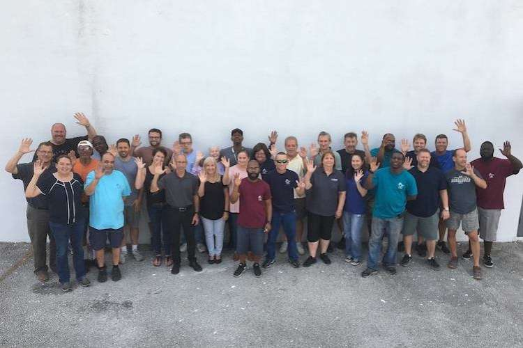 The Lewis Marine Supply team waiwing their hands