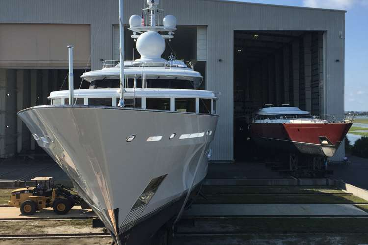 A superyacht dry docking in front of a shipyard hangar