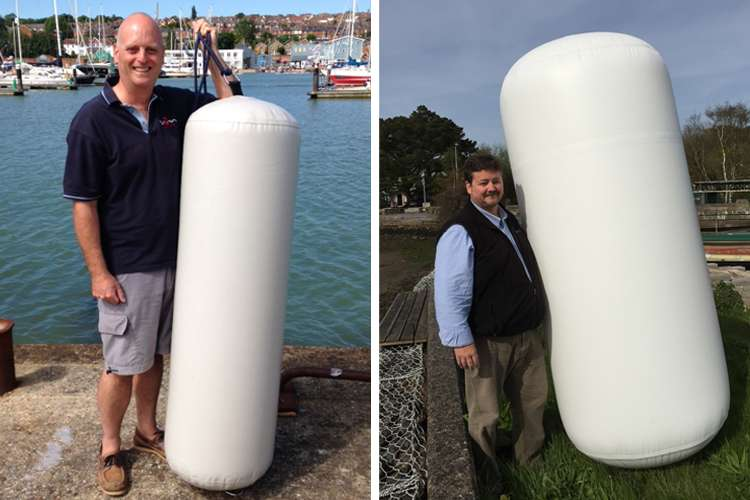 Two men standing and holding white M2M fenders.