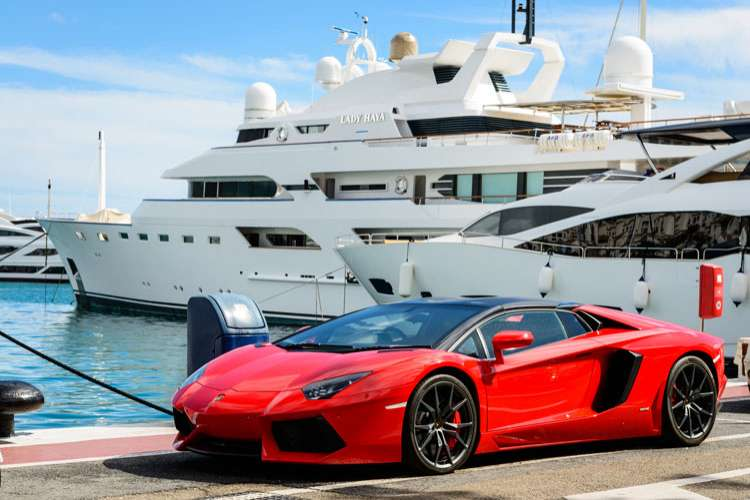 A red Lamborghini parked in front of superyachts in a port.