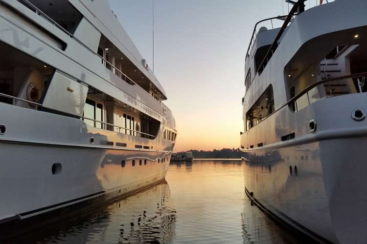Two superyachts berthing in a sunset