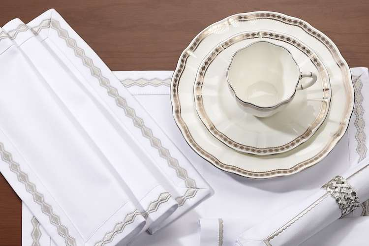 Fine coffee cup china and a saucer set on white heirlooms table linen.
