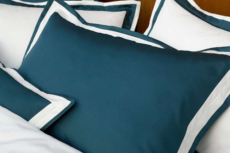 Bed made with green blue and white bed linen