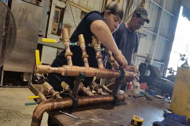 Image of man and a woman working in a Thunderbolt Marine workshop