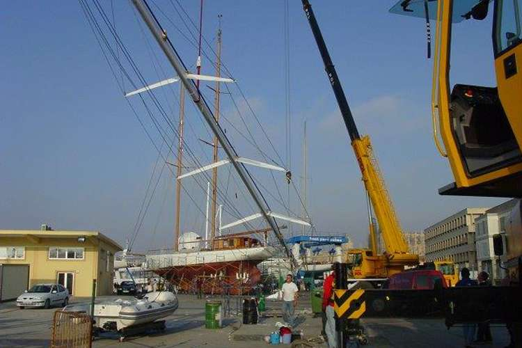 Sailing yacht and lifts in a shipyard.