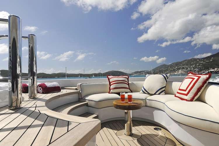 Fitted white sun deck sofas surrounding the swimming pool on superyacht Klaus Jordan