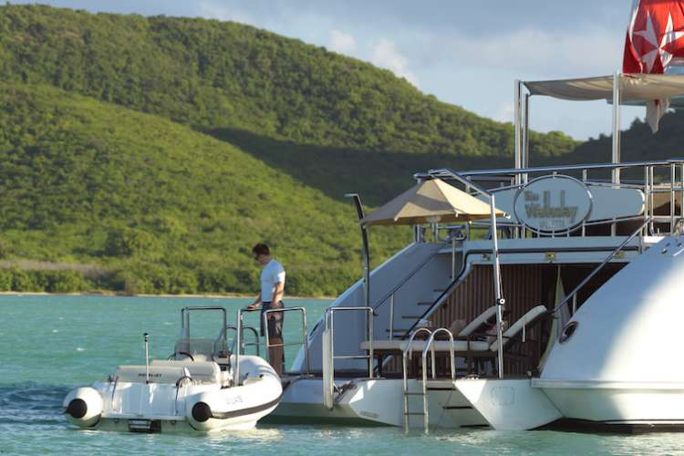 Superyacht crew member standing on the swimming platform looking at a tender