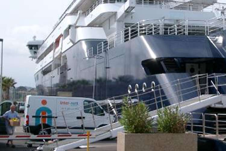 Two white Inter-nett vans parked in a port with a mega yacht in the background