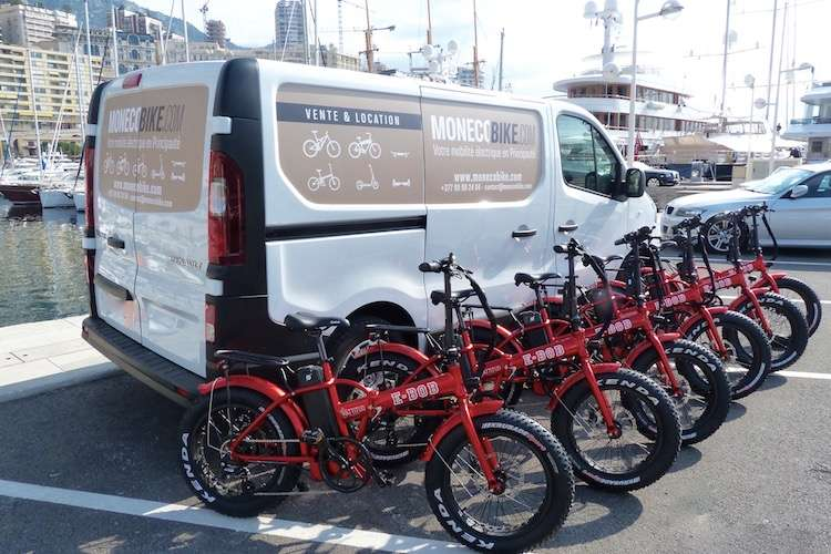 MonecoBike van parked in port of Monaco with red rental e-bikes in a row in front of the car