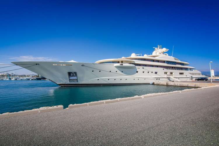 Image of a white mega yacht berthing in a port.
