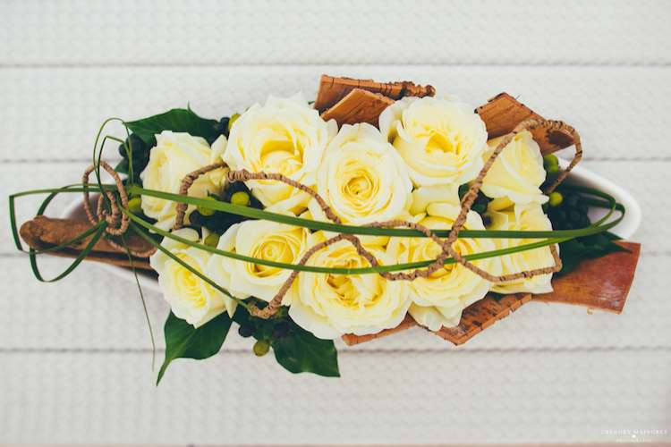 Flower arrangement of yellow roses on a superyacht deck table