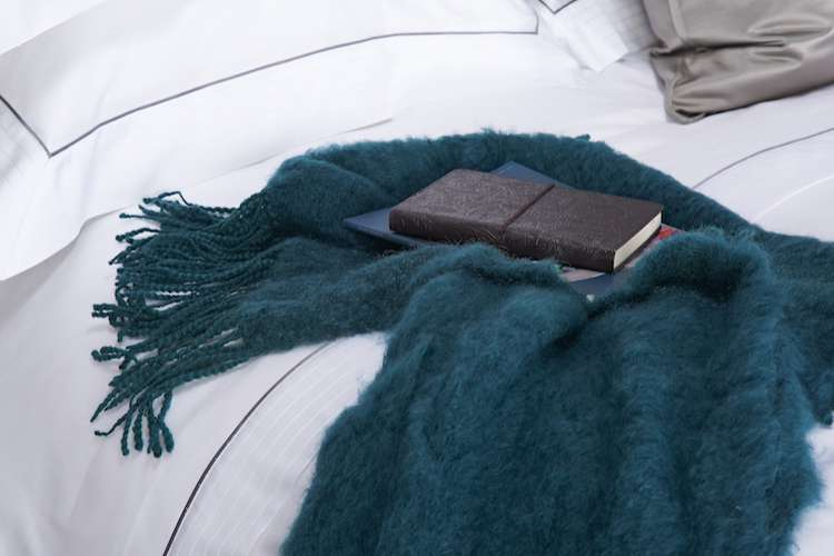Dark green blue mohair blanket on white bed linen