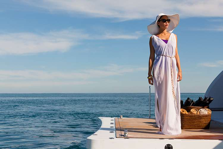Woman wearing a white dress and a hat standing on the stern of a superyacht.