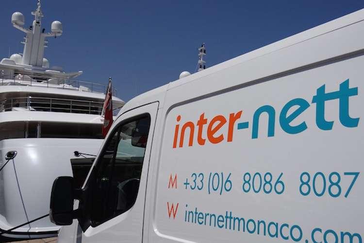 Inter-nett van parked in a port next to a superyacht