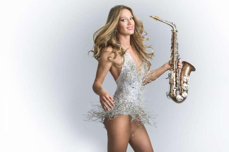 Blond woman wearing short light grey dress holding saxophone.