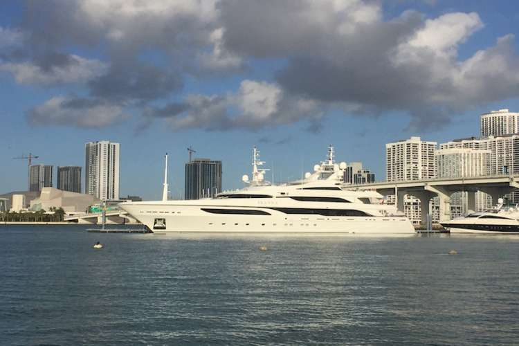 Superyacht anchored in front of a city.