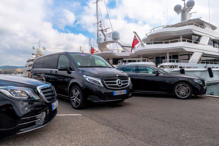 Mercedes cars parked in front of a berthing superyacht