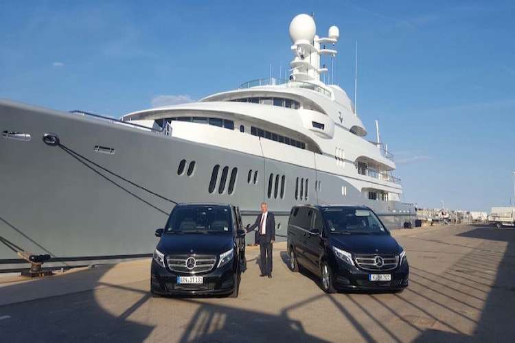 Two Ruby Services black Mercedes vans in front of a superyacht