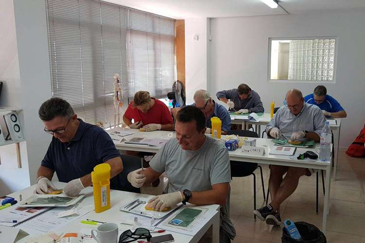 People sitting in a class room participating to a practical medical training.