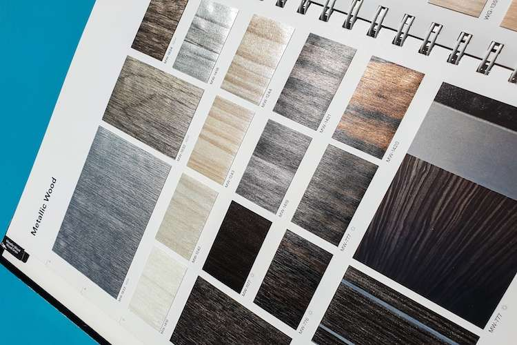 Image of a catalogue of wrap film samples of metallic wood in different colours