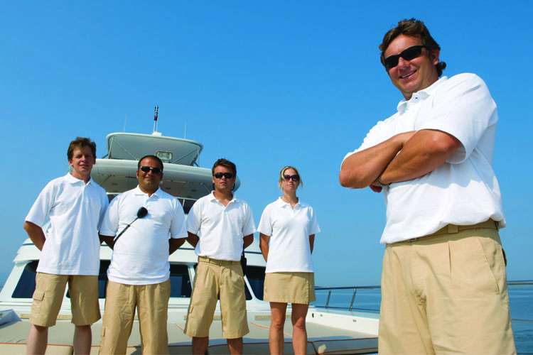 Superyacht crew members smiling and standing in a row on sundeck.