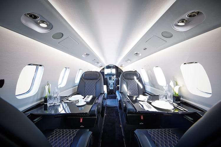 Private jet interiors with black leather seats and tables set for dinner