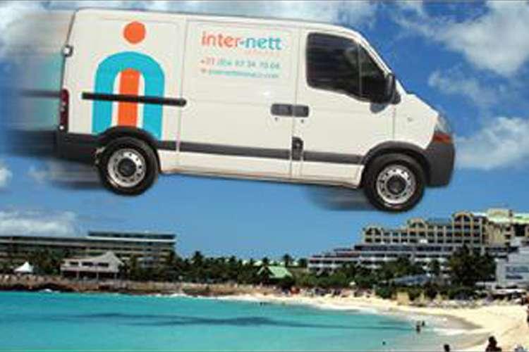 Image of a white Inter-nett van flying over the sea