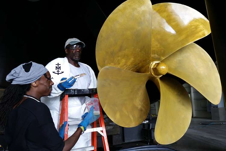 Two men applying a surface treatment on a propeller