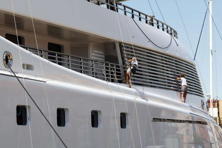 Crew cleaning mega yacht windows over the side.
