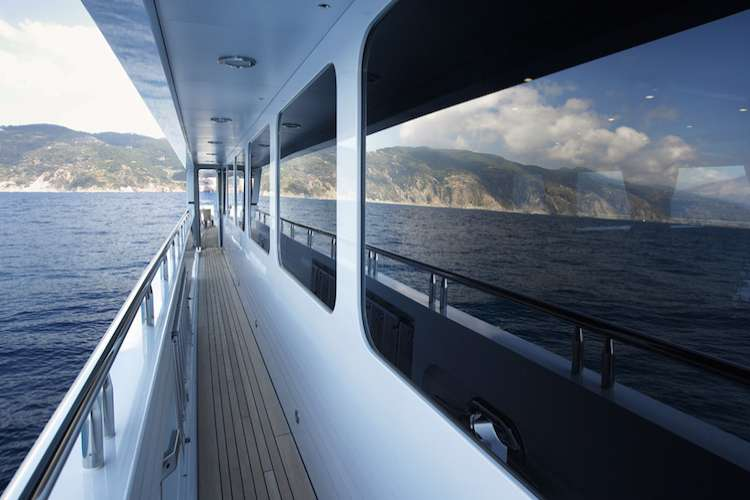 Superyacht deck with the sea mirroring on the windows.