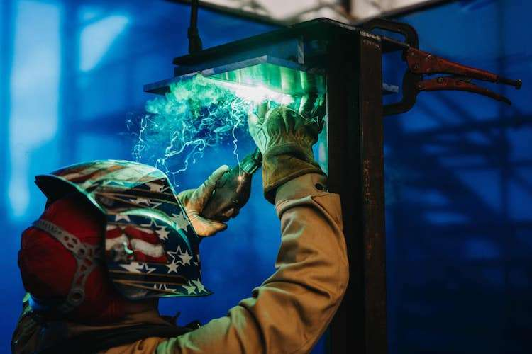 Image of a man welding with protection gear on