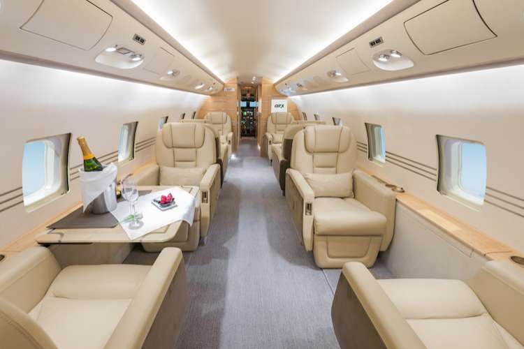 Private jet interiors with beige leather seats and table set for dinner