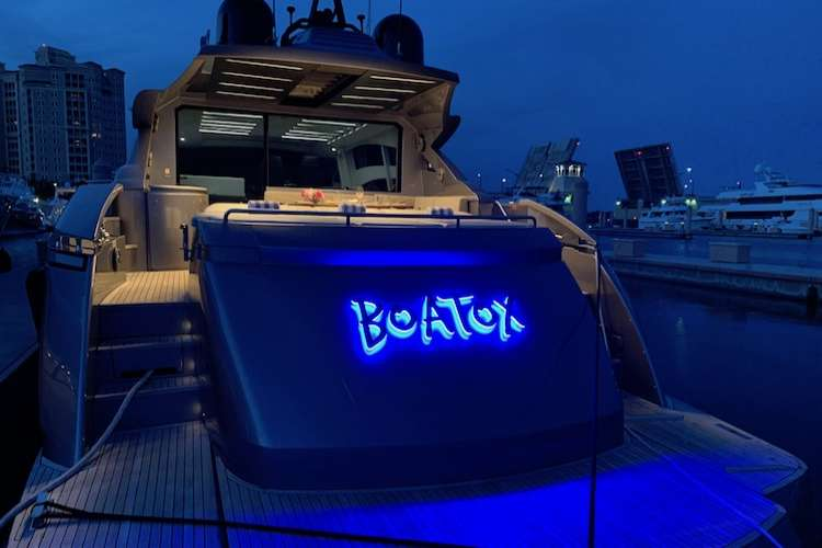 Yacht lettering illuminated in the evening on superyacht Boatox