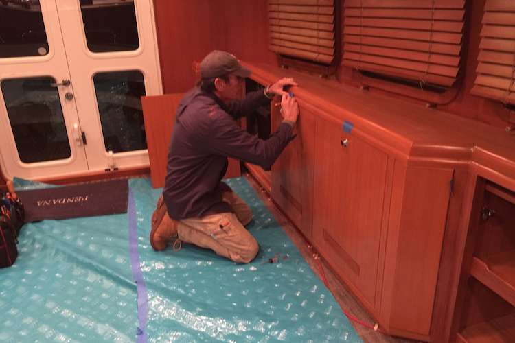 Management carpenter installing custom cabinets in a yacht
