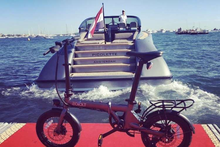 A folding bike from MonecoBike on a red carpet in a port with a yacht departing in the background