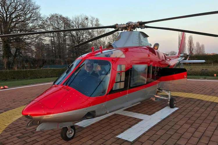 Red helicopter with its captain sitting inside