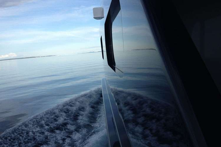 Calm sea and horizon mirroring from a superyacht hull.