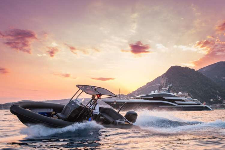 Man cruising on a Ribeye tender in a sunset with a superyacht in the background